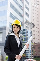 Businesswoman holding blueprint and looking at the camera with helmet