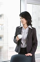 Businesswoman holding a cup and looking away, portrait