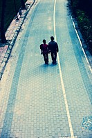 two people walking in the old river bed of Turia River, Valencia, Spain