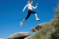 Woman running over rocks (thumbnail)