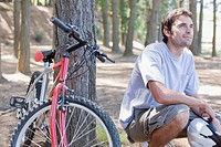 Bike rider relaxing in forest