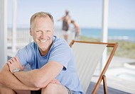 Man sitting on deck smiling