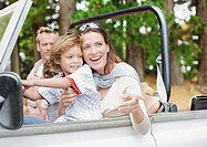 Father, mother and son riding in jeep
