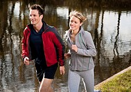 Couple jogging near pond