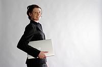 762308 Junge Frau in schwarzem Nadelstreifen_Anzug mit Laptop unter dem Arm