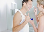 Woman putting face cream on husband's face