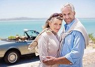 Couple standing near convertible