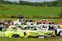 cars participate in a demolition derby with on-lookers in a pasture