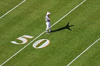 referee makes a call at the 50 yard line of a football game