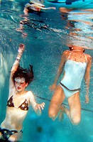 Female swimmers frolic underwater.Wearing Bikinis and jewelry.editorial use only.2003 Photography David Ewing