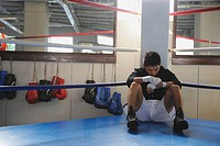 Japanese boxer sitting in corner of Boxing ring