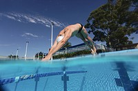 Young swimmer diving into swimming pool