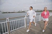 Young couple jogging on bridge