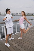 Young couple Exercising,and stretching on Bridge