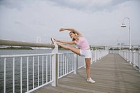 Young Woman stretching legs on Bridge