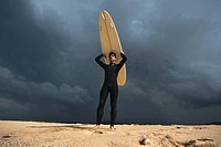 Surfer standing on beach and holding surfboard above his head