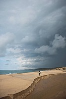 Man walking on sand with his surfboard on stormy day