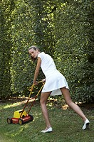 Junge Frau ganz in weiss mit Rasenmaeher im Garten, young woman clad all in white with a lawnmower in the garden