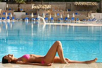 Woman tanning and swimming pool