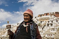 Woman praying with monastery in the background, Thiksey Monastery, Ladakh, Jammu and Kashmir, India