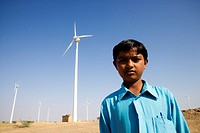 Portrait of a boy with wind turbines in the background, Jaisalmer, Rajasthan, India
