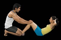 Male instructor helping woman in doing sit_ups