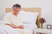 Senior woman with eyes closed sitting on bed