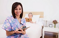 Portrait of smiling nurse holding clipboard, senior woman lying in bed in background