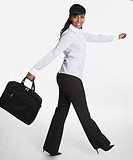 Businesswoman with briefcase walking in studio