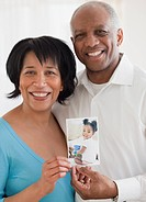 African couple holding photo of granddaughter