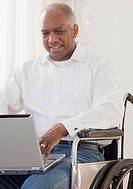 African man in wheelchair using laptop