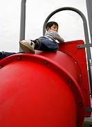 boy climbing playground equipment