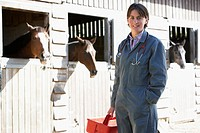 Portrait Of Vet Standing By Horse Stables