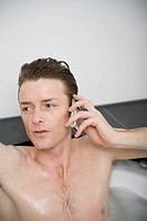 Man sitting in a bathtub and holding a mobile phone