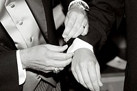 A man helping a groom with his cufflinks