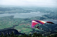Hang glider flying over rural landscape