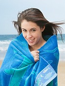 Mixed race woman wrapped in a towel on beach