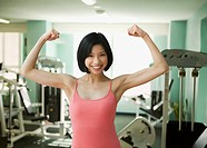 Filipino woman flexing biceps in health club