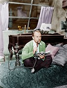 Man sitting on a bed smoking his water pipe Old Visuals