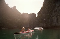 People kayaking in water near rock formation