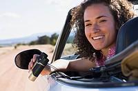 Mixed race woman holding binoculars in convertible