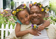 African grandfather and granddaughter hugging with flowers on head