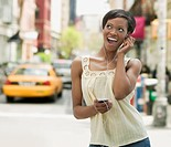 African woman on urban street listening to headphones