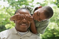 African grandson covering grandfather´s eyes
