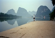 Man standing at the edge of a lake in front of rock formations, Yangshou, China
