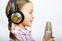 A girl wearing headphones and holding a microphone