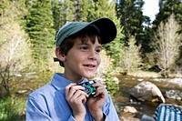 A young boy holding a disposable camera by a river