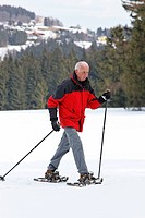 Elderly man in winter snow shoe hiking