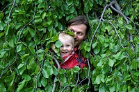 A father and son hiding in a bush