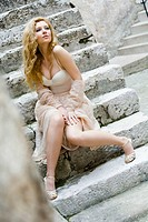 Pretty young woman in wedding dress is sitting on stone staircase and showing bare knees